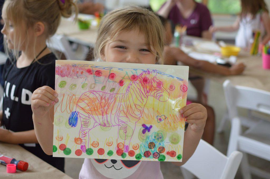 A young girl holding up an artwork made during an art class